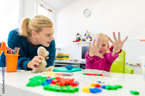 Toddler girl in child occupational therapy session doing sensory playful exercises with her therapist Fototapeta
