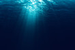 perfectly seamless of deep blue ocean waves from underwater background with micro particles flowing, light rays shining through