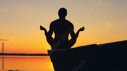 Yoga, man meditatiing in lotus pose on the beach near the sea, ocean, during sunset