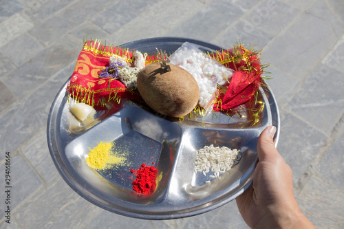 Hand holding offerings to Shiva in metal plate - coconut, trident, turmeric, flowers. Close-up, copy space