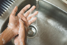 Closeup Of A Boy Scrubbing Soapy Hand Against Washbasin. Concept Of A Hand Hygiene And Global Handwashing Day