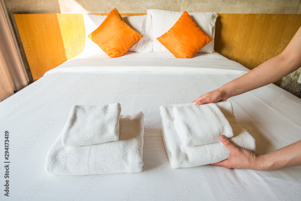 Fototapety, obrazy: Close up of hotel maid arranging the set of towels on bed. Conceptual of female chambermaid making bed in hotel room.