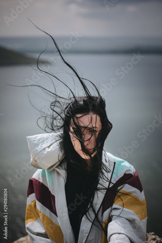 Leinwand Poster Stylish hipster girl with windy hair sitting on top of rock mountain with beautiful view on river