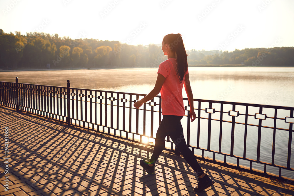Fototapety, obrazy: Back view of a runner walking on a road in a park