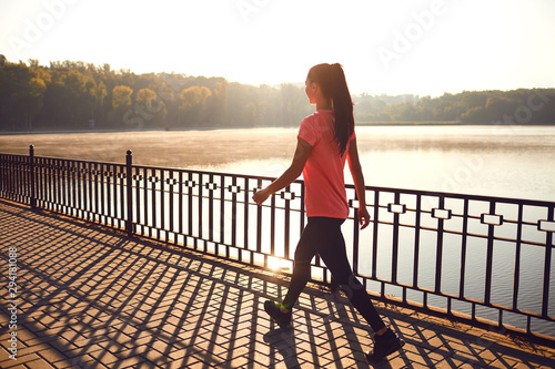 Obraz Back view of a runner walking on a road in a park - fototapety do salonu