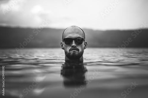 Brutal bearded man in sunglasses emerge in lake waves Fototapet
