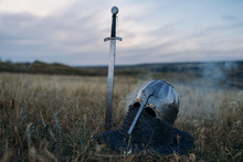 Sword Stuck In The Ground And Metal Knight Helmet