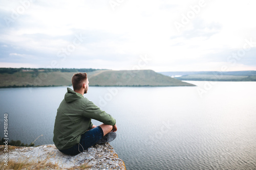 Photo Hipster traveler sitting on top of rock mountain and enjoying amazing view on river