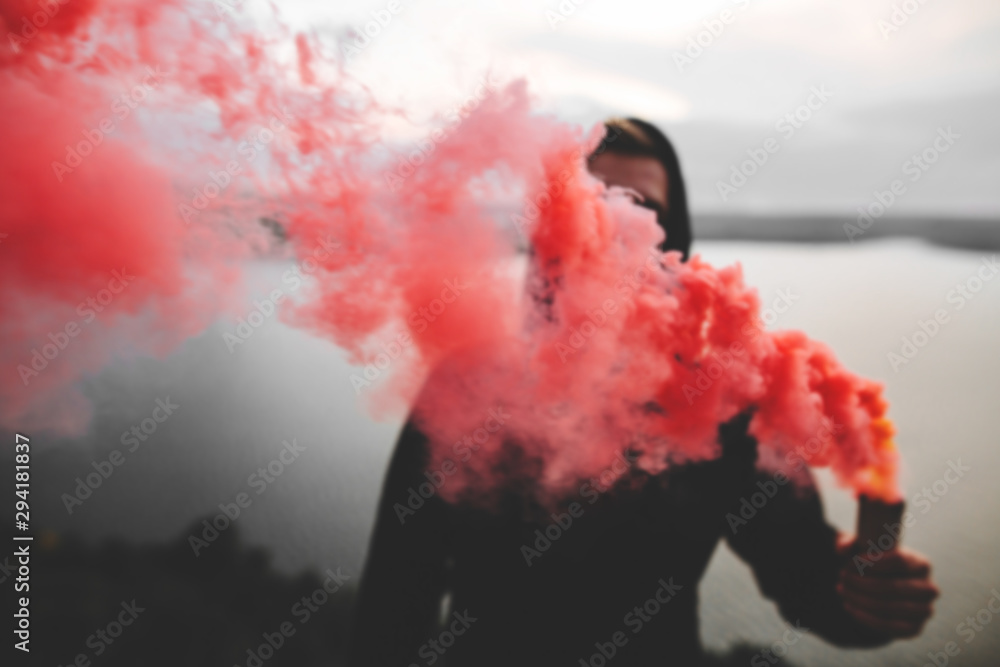 Fototapety, obrazy: Red smoke bomb. Blurred image of ultras hooligan holding  smoke bomb in hand, standing on top of rock mountain with amazing view on river. Atmospheric moment. Copy space