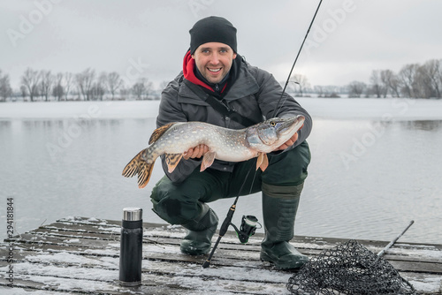 Obraz Winter fishing. Happy fisherman with pike fish at wooden platform. - fototapety do salonu