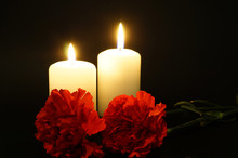 Two Burning Candles With Flowe...