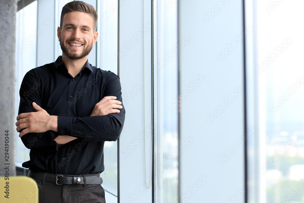 Fototapeta Modern business man is standing near window in the office
