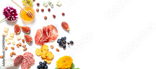 Antipasti food white flat lay with nuts, honey, cured meat, salami, cheeses, grapes and figs Canvas Print