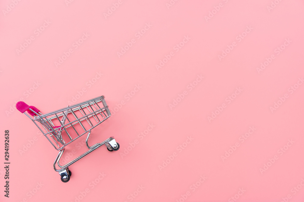 Fototapeta Empty shopping cart on pink background. Shopping, shopping online concept.,copy space, top view