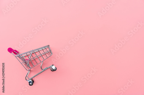 Empty shopping cart on pink background Fototapeta