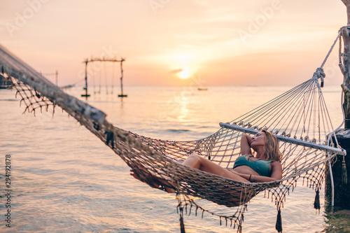 fototapeta na lodówkę Girl relaxing in hammock on sunset beach
