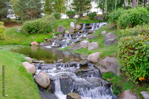 Foto auf Gartenposter Forest river Landscape with a forest waterfall. Water runs on the rocks to the bottom forming a small pond.