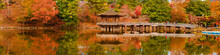Scenic View Of Nara Public Park In Autumn, With Maple Leaves, Pond And Old Oriental Pavilion Reflected In The Water