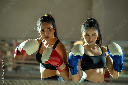 Two women wearing boxing gloves training boxing.Boxing practice at gym.Woman in sports clothing preparing for boxing fight or workout.