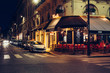 canvas print picture - Cozy street with tables of cafe in Paris at night, France