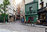 Fototapeta Uliczki - Cozy street with tables of cafe in Paris, France