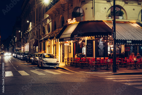 Vászonkép  Cozy street with tables of cafe in Paris at night, France