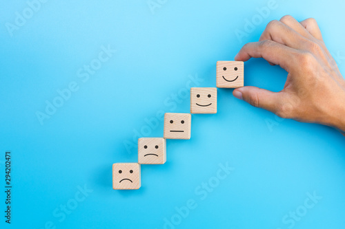 Fototapeta Customer service evaluation, satisfaction survey and best excellent services rating concept. The client's hand picked the happy face smile face symbol on wooden blocks, copy space obraz na płótnie