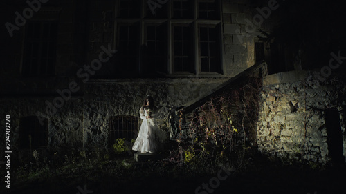 Photo  On the night of Halloween bride coming down the stairs of old abandoned medieval