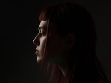 Portrait Of Young Woman In Profile. Low Key