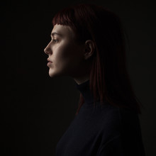 Portrait Of Young Woman In Profile. Low Key. Close Up