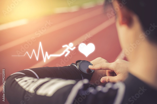 Valokuva  Women measuring heart rate with a watch after running