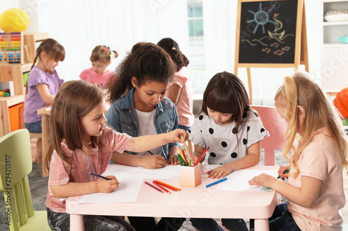 Poster Individuel Adorable children drawing together at table indoors. Kindergarten playtime activities