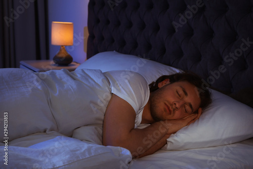 Handsome young man sleeping on pillow at night. Bedtime Canvas Print
