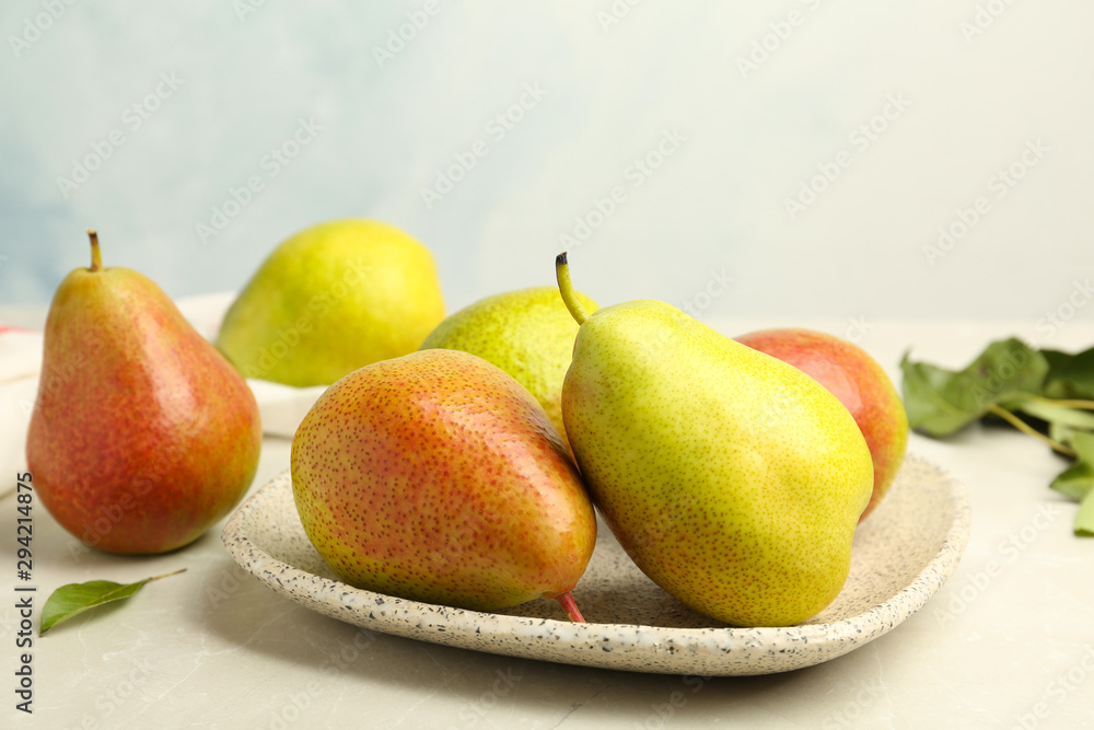 Fototapety, obrazy: Plate with ripe juicy pears on stone table against light background
