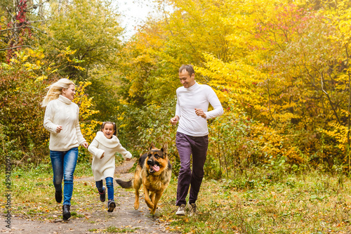 Obraz Happy family with children running after a dog together in autumn park - fototapety do salonu