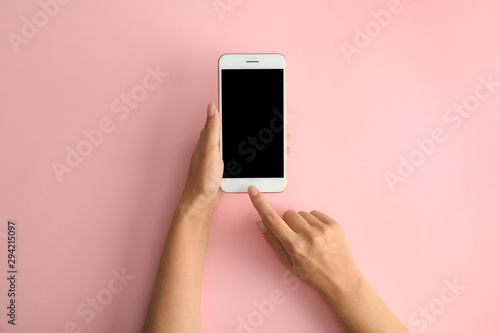 Fotografía Woman holding modern phone on pink background, top view