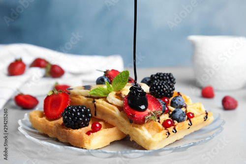 Pouring sauce onto delicious waffles with fresh berries served on grey table
