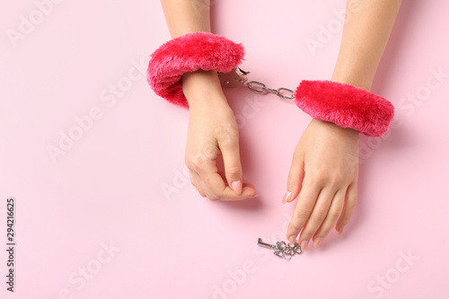 Obraz Young woman with fluffy handcuffs and keys on pink background, top view with space for text. Sexual role play accessory - fototapety do salonu