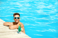 Happy Young Man With Cocktail In Swimming Pool