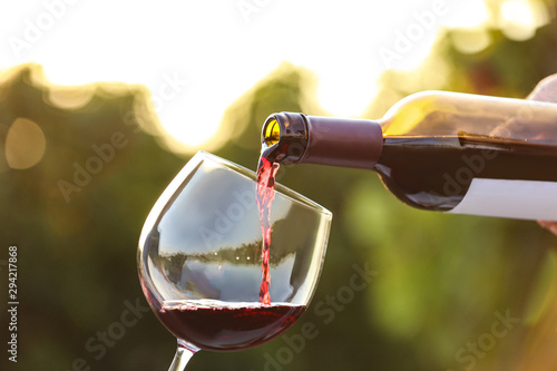 In de dag Alcohol Woman pouring wine from bottle into glass outdoors, closeup