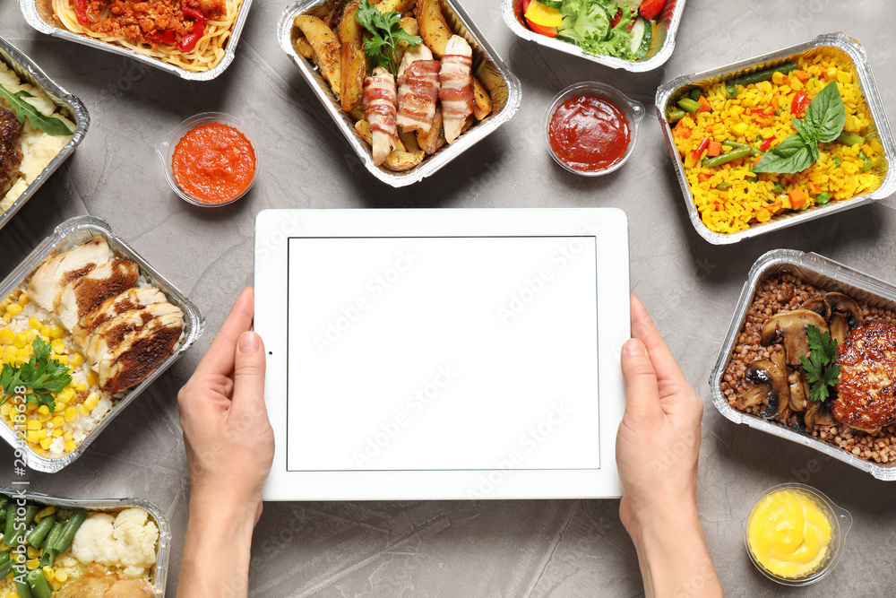 Fototapety, obrazy: Top view of woman holding tablet over grey table with lunchboxes, mockup for design. Healthy food delivery