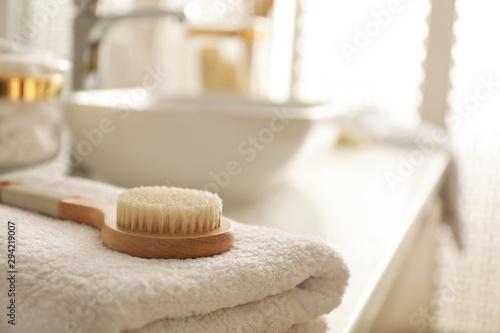 Fototapeta Hairbrush on towel on countertop in bathroom obraz