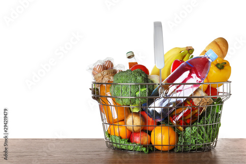 Cuadros en Lienzo Shopping basket with grocery products on wooden table against white background