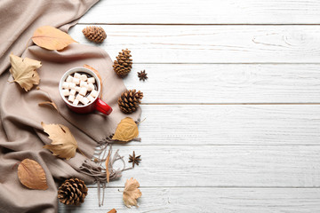 Flat lay composition with cup of hot drink on white wooden table, space for text. Cozy autumn atmosphere