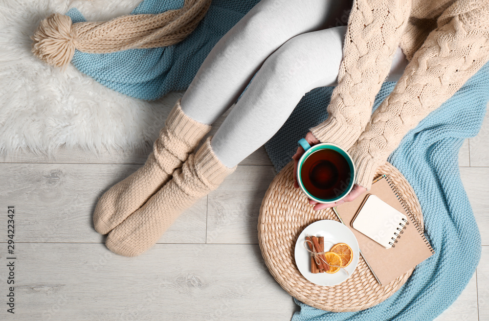 Fototapety, obrazy: Woman and cup of hot winter drink on floor at home, top view