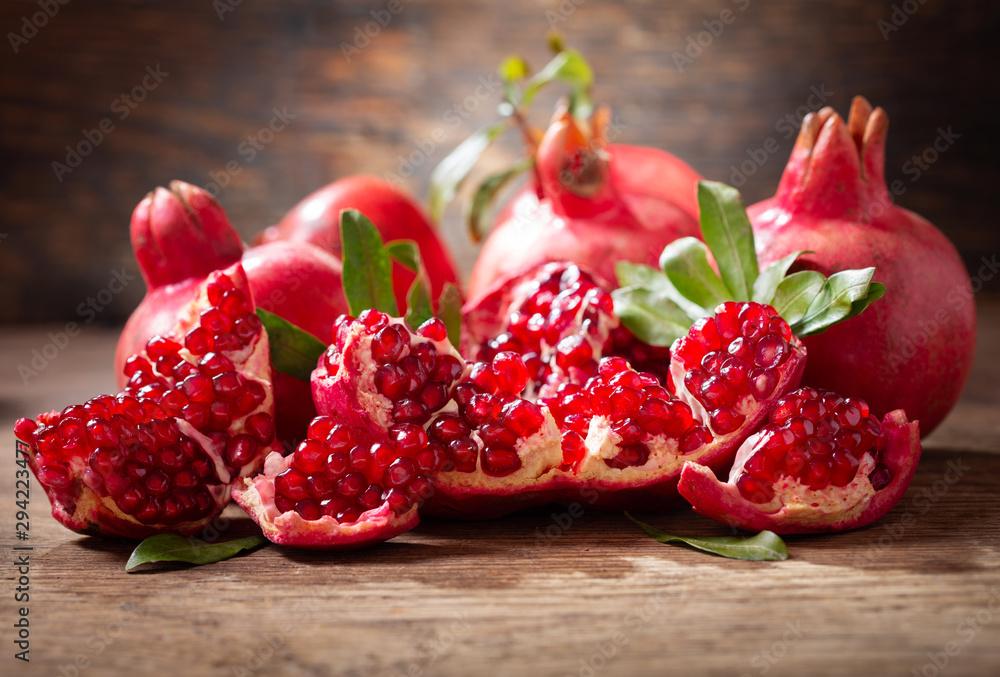 Fototapeta fresh ripe pomegranates with leaves