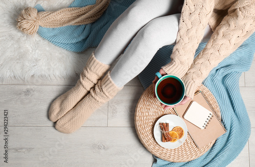 Cadres-photo bureau Fleur Woman and cup of hot winter drink on floor at home, top view