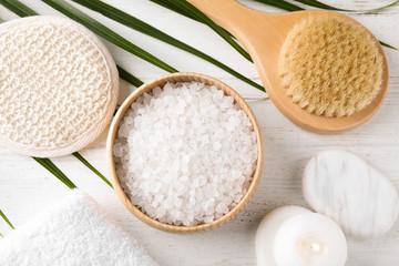 Fototapeta na wymiar White sea salt and supplies for spa scrubbing procedure on wooden table, flat lay