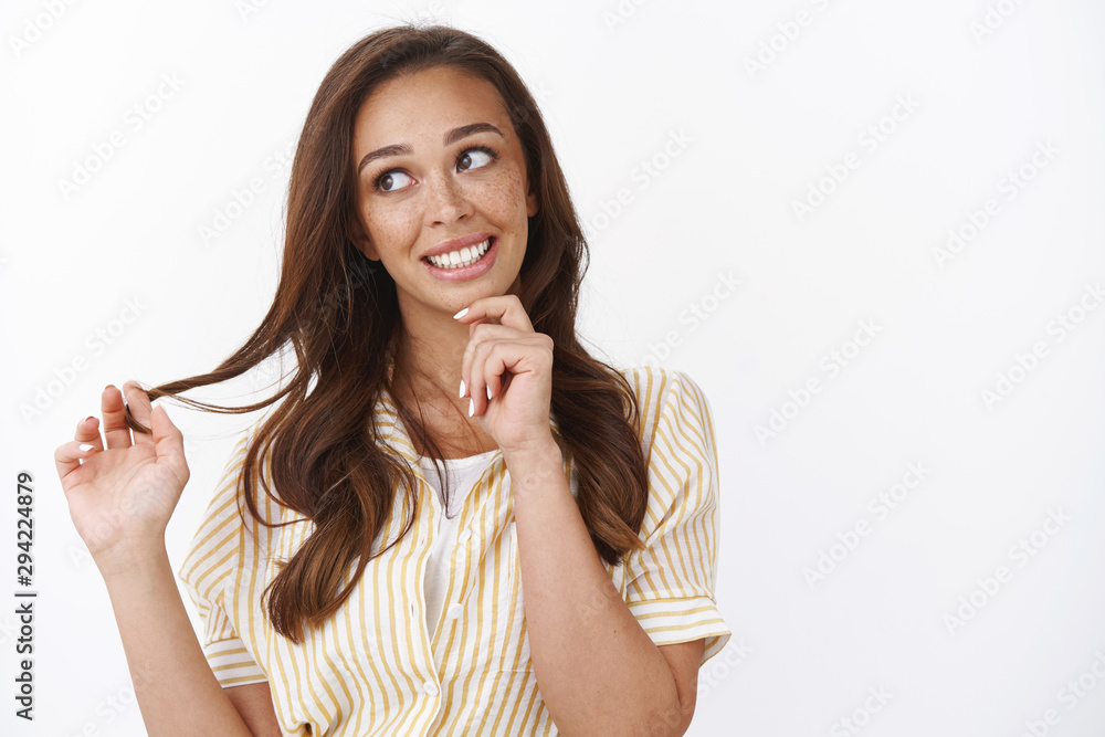 Fototapety, obrazy: Waist-up shot silly, coquettish young woman with long brown hairstyle, smiling avoiding eye contact, looking sideways and grinning flirty, acting playful, rolling curl on finger, white background
