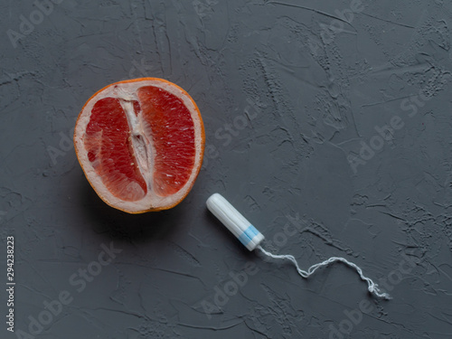 Photo concept. red grapefruit and tampon